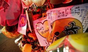 Notes, flowers and balloons are left at a makeshift memorial near the spot where former New Orleans Saints defensive end Will Smith was shot and killed.
