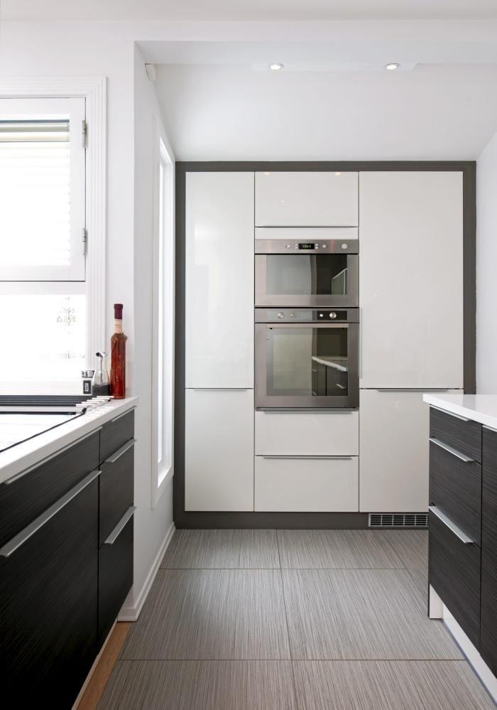 Hvitevarene er integrert i kjøkkeninnredningen, og fremstår som rammet inn av en grå kant som skiller veggen fra kjøkkeninnredningen.