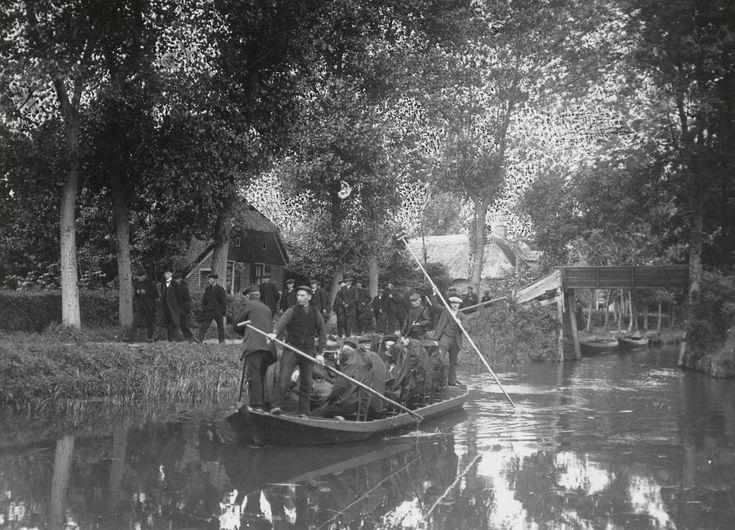 Begrafenis per punter. Op de punter zitten de vrouwen en enkele mannen in Giethoornse streekdracht rond de kist. De overige mannen lopen op het pad langs het water. Allen dragen begrafeniskleding. #KopOverijssel