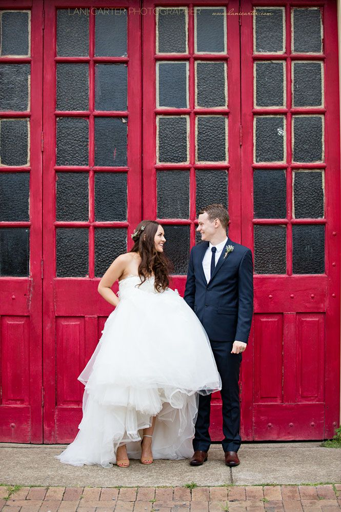Bride and groom show off shoes in front of the red doors at Old Petrie Town, Brisbane. www.lanicarter.com