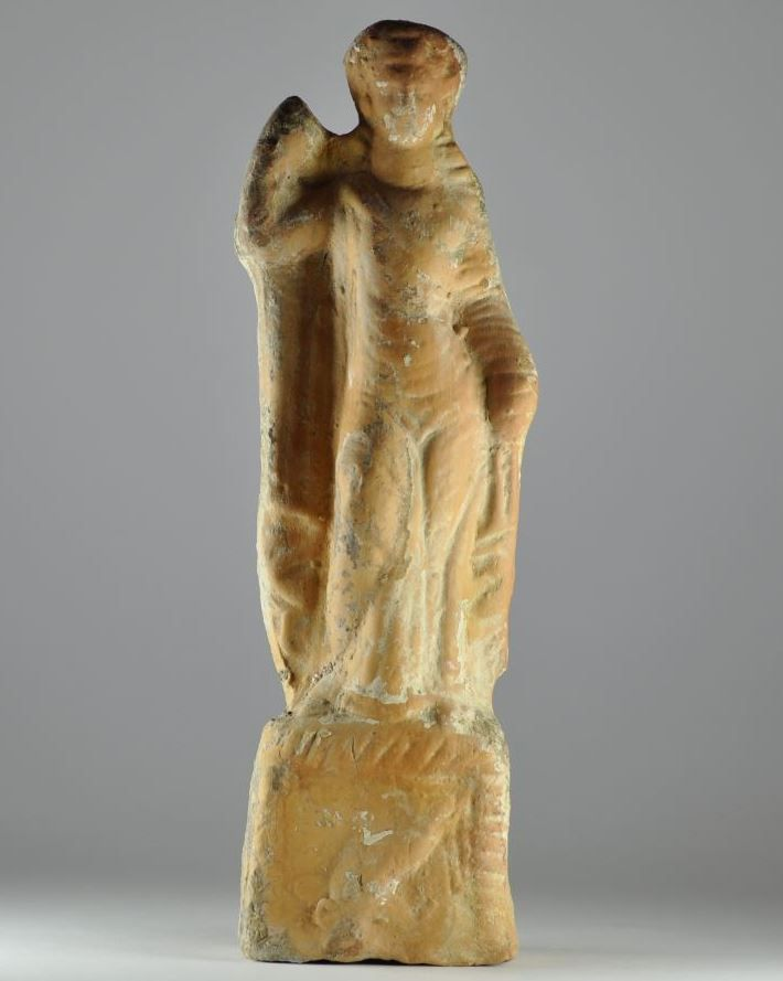 Greek Tanagra figurine, 2nd century B.C.  Hollow cast terracotta figurine of a loosely draped female on a rectangular base decorated with dolphin, 20 cm high. Private collection