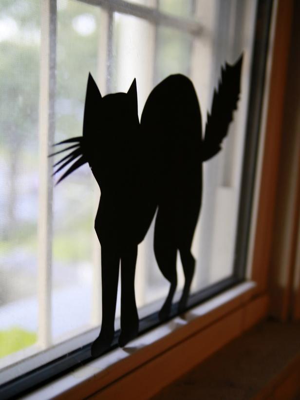 Gatos negros.  Dibújalo en hojas negras y recórtalos. Pégalos en las ventanas o en tu cerca.