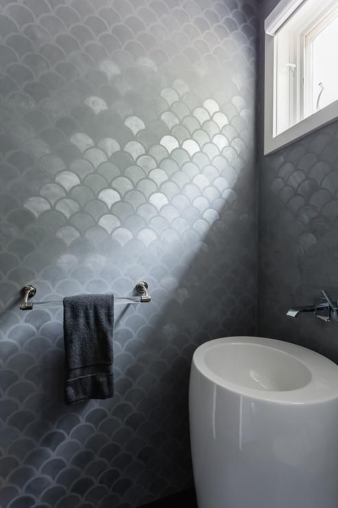 Modern gray bathroom features walls clad in gray metallic fishscale tiles lined with a modern white pedestal sink which resembles an egg under a wall mount faucet.