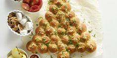 Zelf gebakken brood in de vorm van een kerstboom met gesmolten kruidenboter en geraspte oude kaas.
