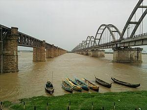 Godavari del puente a la izquierda y Puente de Arco Godavari a la derecha. El puente es un puente fuera de servicio que abarca todo el río Godavari en Andhra Pradesh , India .