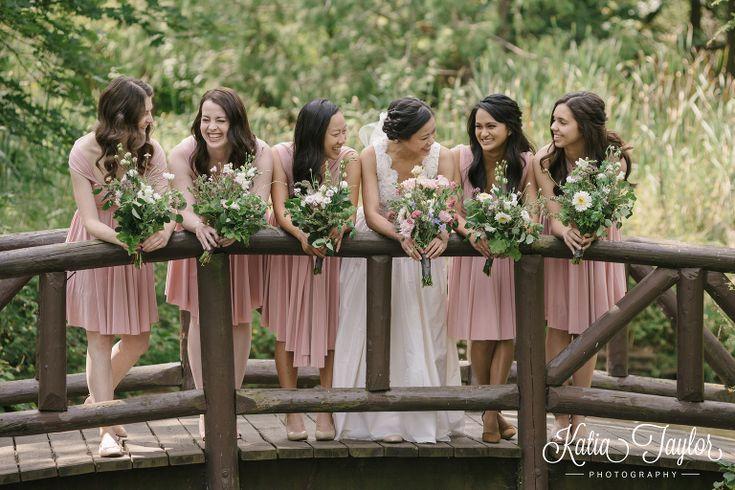 Bride with bridesmaids on bridge. Soft pink dresses. James Gardens, Toronto wedding photography.