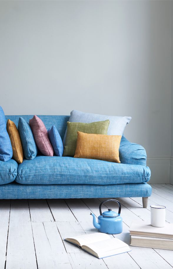 Loaf's deep and comfy Hunker sofa in bright blue linen with relaxed pleats and colourful Mid-century scatter cushions
