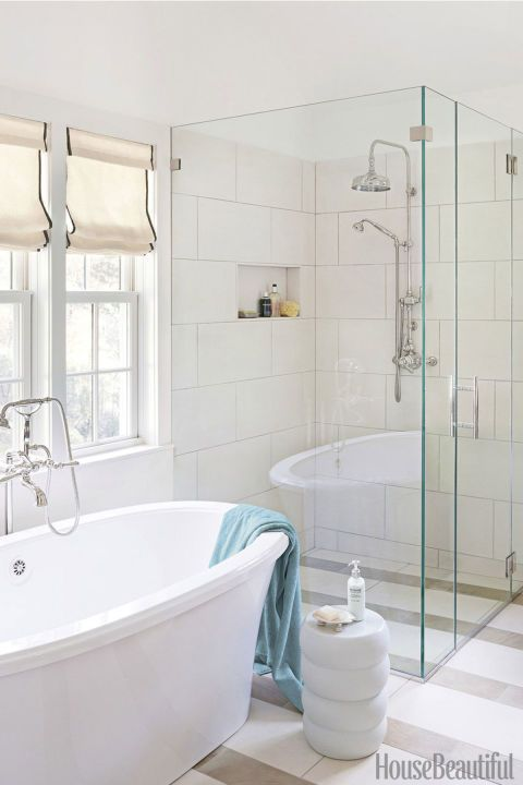Calm and serene, this bathroom is a light-filled respite from a busy world. The limited color palette and sleek forms inviterelaxation. We especially love the striped tiles,open, free-standing tuband glassshower.