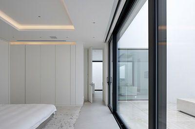 Hlavní ložnice v suterénu má výhled do atria.
