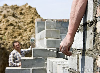 Two house builders checking if the wall is even. One is holding a nail with a string attached, the other is holding another end of the string.  <a href='http://www.dreamstime.com/interiors-rcollection5192-resi208938' STYLE='font-size:13px; text-decoration: blink; color:#FF0000'><b>HOME BUILDING & RENOVATION »</b></a>