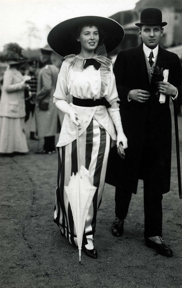 1912 or 1913. That skirt! She looks so absolutely beautiful, from 100 years ago.... At the races. Woman in long striped skirt with belted jacket , and big hat and umbrella, man in overcoat, bowler hat, spats, gloves and cane. Place unknown, in 1912 or 1913. Posted by article in Life in 1929, looking back with wonder at the fashions of 15 years ago.