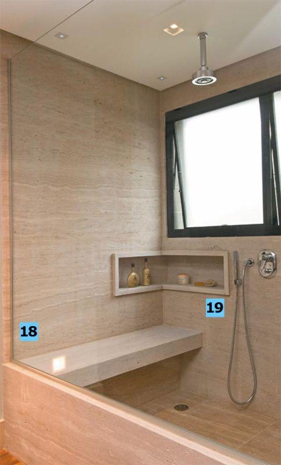 """18. O boxe, grande (1,35 x 1,35 m) e confortável, é um dos atrativos do espaço. A 45 cm de altura, fica um banco de travertino que """"serve para apoiar e lavar os pés"""", exemplifica Flávio. O nicho completa a lista de mimos: alcança 10 cm de profundidade, o mínimo necessário para acomodar frascos e vidrinhos. 19. Além do chuveiro de teto, o banheiro oferece uma duchinha (Deca), acionada pelo mesmo misturador monocomando. """"Essa associação é prática: nem sempre as mulheres querem molhar os…"""