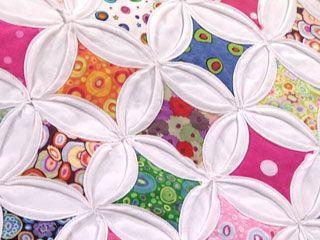 Na junção dos quadrados, coloque os quadradinhos coloridos com o direito para cima. Dobre o tecido branco sobre cada borda de cor para marcar a janela, colocando alfinetes. Costure à mão com costura oculta ou bainha pequena que fique à mostra, pegando todas as camadas de tecido, ou então à máquina. Uma vez acabadas todas as filas, una-as umas às outras da mesma forma.Observação:Este bloco não precisa ser quilteado quando estiver acabado. Também não levará tecido nem manta acrílica por…