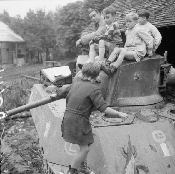 Gacé, 23 August 1944: French chilren climb aboard a Free French M3A3 Stuart tank.
