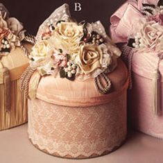 """12"""" round hat box with lace on a moiré base and a beautiful floral arrangement on top."""