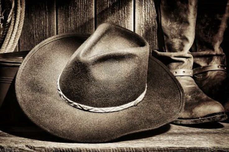 American West rodeo cowboy felt hat and authentic leather western riding boots with vintage ranching gear on weathered wood floor in an old ranch barn  Stock Photo