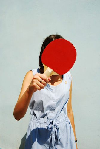 Woman Covering Face With Table Tennis Racket Against Wall