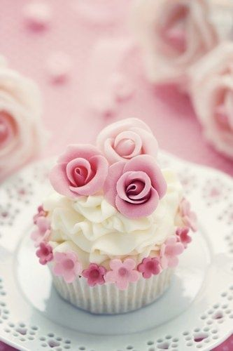 Cupcake with white frosting and pink sugar flowers