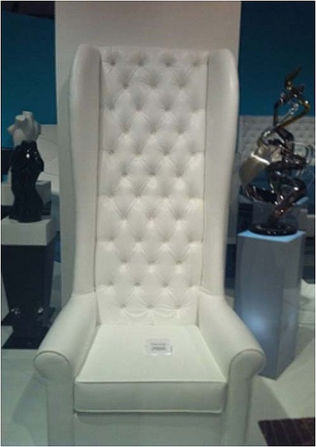 4013 WHITE VELVET OVERSIZE CHAIR TUFTED WITH CRYSTALS  Whether you're a rockstar or a glamazon, this chair is for you. The velvet high back is fun and interesting and makes it a dramatic addition to your house. The wings enclose you slightly while seated, making it extremely cozy and comfortable to sit in. It is then finished off with a generous helping of dazzling Swarovski crystals that turn up the glamor and sparkle in the light. This chair brightens up and adds some fun to any room.