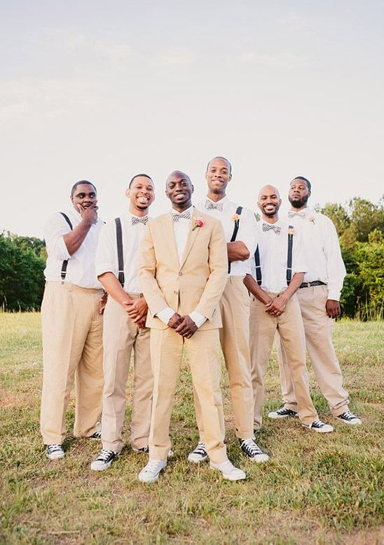 Beige pants, white button down shirts paired with matching striped bow ties and black suspenders, black converse shoes and peach rose boutonnieres. Wedding style: retro backyard; Wedding colors: teal and white. Photo by Our Labor of Love, check out more here.