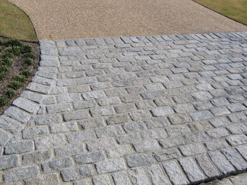 Granite cobblestone apron with soldier banding, together with a classic pea- gravel aggregate driveway with upturned edges. The entrance to an exquisite master landscape plan designed by the award- winning firm, Land Plus.