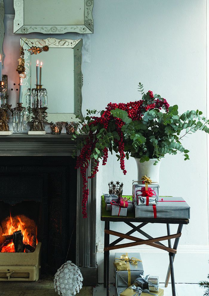 A vase of fragrant eucalyptus and bright red berries makes a beautiful gathering spot for wrapped gifts.  Courtesy of Farrow & Ball.