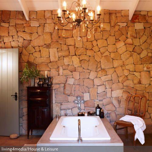 die natursteinwand passt zu dem lndlichen chic des badezimmers hier trifft die moderne freistehende badewanne