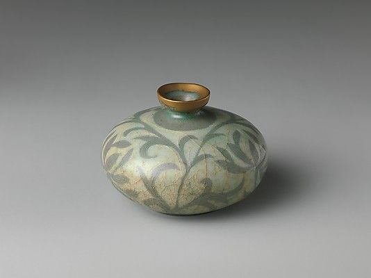 Oil bottle. Goryeo dynasty (918–1392) late 12th century Korean stoneware with reverse-inlaid decoration of peony leaves under celadon glaze. The Metropolitan Museum of Art.
