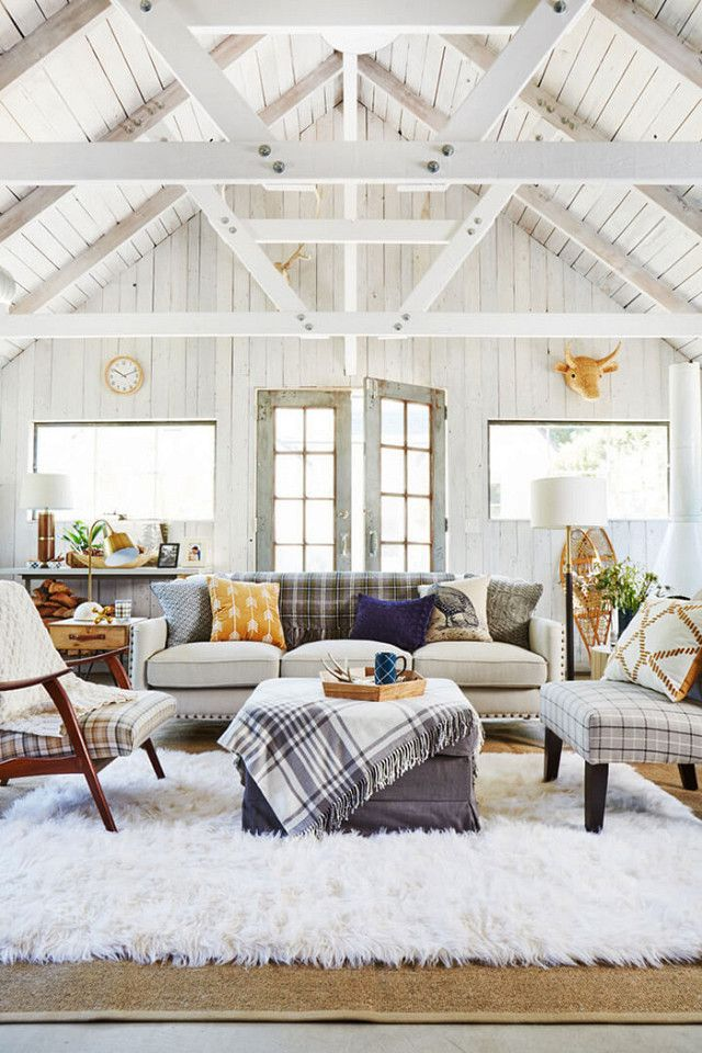 Rustic-inspired living space with high ceiling beams, a large plush rug, and matching armchairs