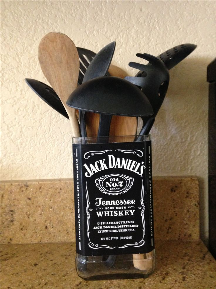 Repurposed Jack Daniels bottle to hold cooking utensils next to the stove.