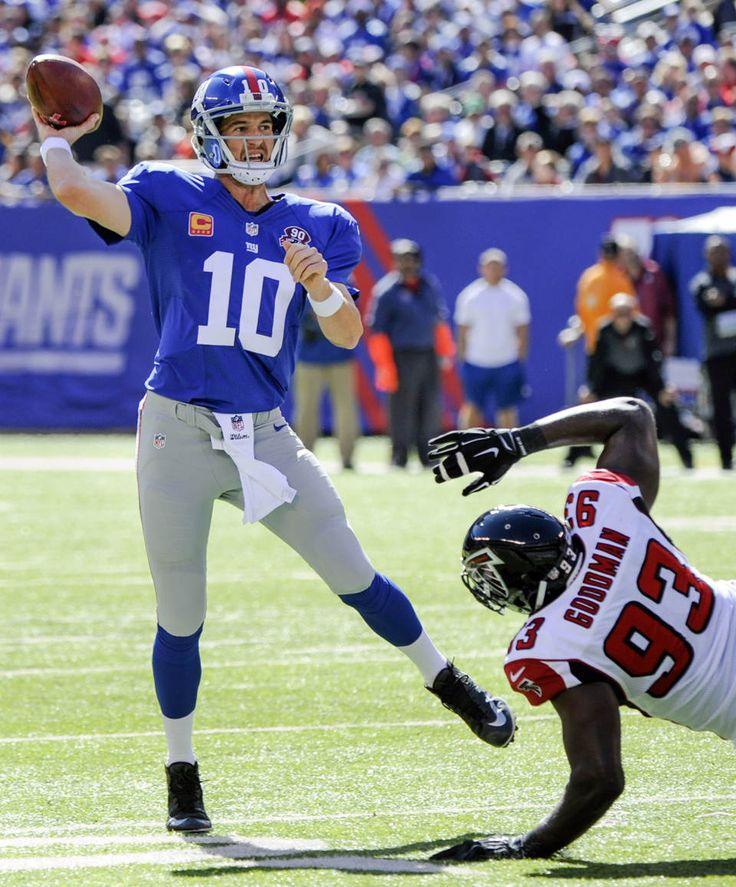 Giants win third straight behind Beckham, Manning - New York Giants quarterback Eli Manning (10) avoids the tackle of Atlanta Falcons defensive end Malliciah Goodman (93) while throwing a pass during the first half of an NFL football game, Sunday, Oct. 5, 2014, in East Rutherford, N.J. (AP Photo/Bill Kostroun)