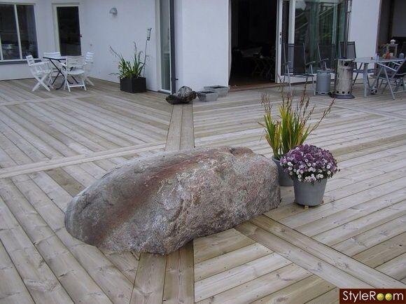 Annorlunda inramning av trädäck/altan med stilrena stilleben i form av stenblock. Lättskött