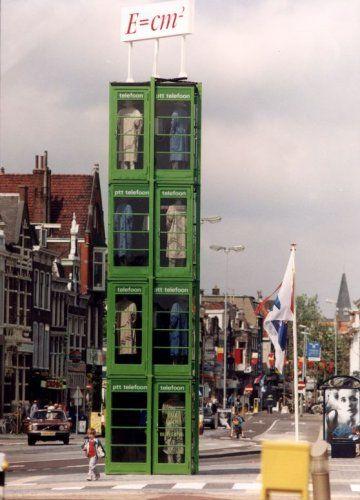 Een kunstwerk, bestaande uit een toren van bezette telefooncellen en een bord E=cm2, genaamd de Body Building, van de Belgische gebroeders Schietekat op het Houtplein in Haarlem. Geplaatst ter gelegenheid van de Frans Halstentoonstelling, 11 mei 1990.