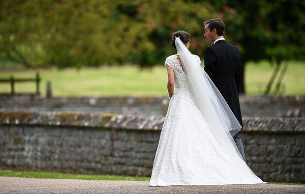 Pippa Middleton Photos Photos - Pippa Middleton (L) and her new husband James Matthews leave St Mark's Church in Englefield, west of London, on May 20, 2017 following their wedding ceremony..After turning heads at her sister Kate's wedding to Prince William, Pippa Middleton graduated from bridesmaid to bride on Saturday at a star-studded wedding in an English country church. The 33-year-old married financier James Matthews, 41, at a ceremony attended by the royal couple and tennis star Roger…