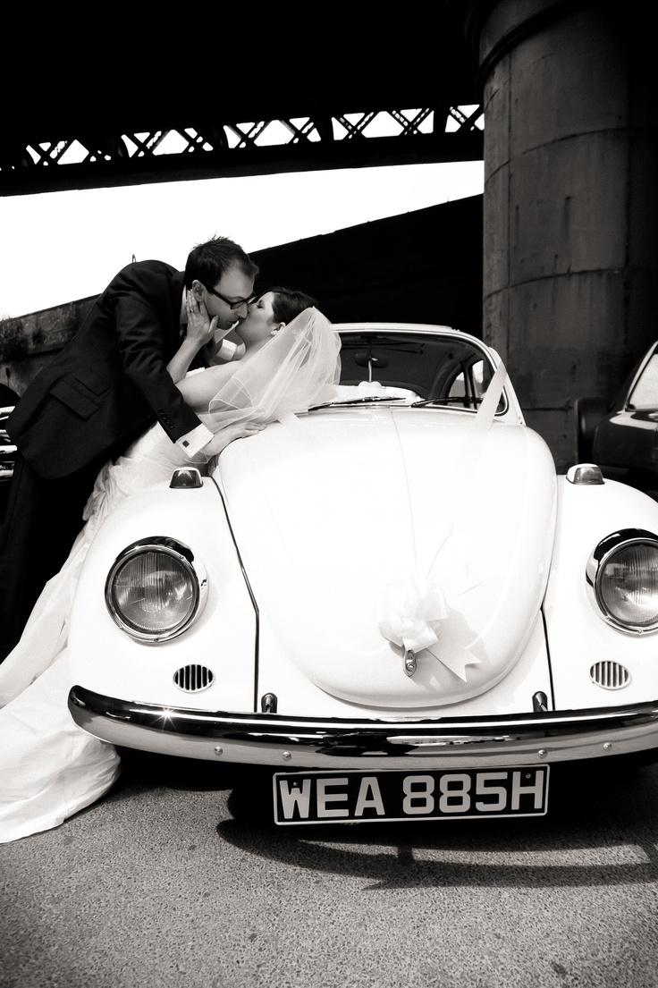 Bride and Groom kiss VW Beetle
