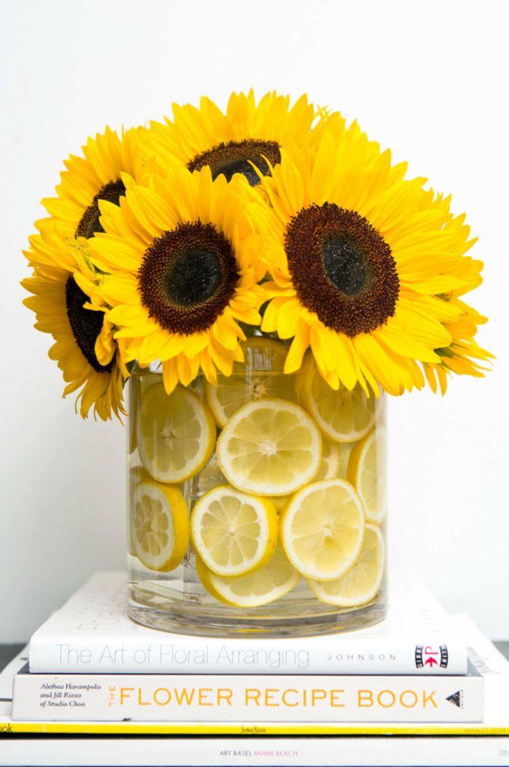 8. Metti un vaso di vetro dentro un altro così da riempire lo spazio in mezzo con delle fettine di frutta. Trova un vaso che puoi infilare dentro a un altro che lasci uno spazio di un centimetro tra i due. Riempi la maggioranza di quello spazio con dell'acqua prima di metterci delle fettine di limone (per la composizione nella foto ne abbiamo usati nove). Inserisci i fiori che vuoi mettere in risalto (nel nostro caso, una dozzina di girasoli) nel vaso centrale e il gioco è fatto…