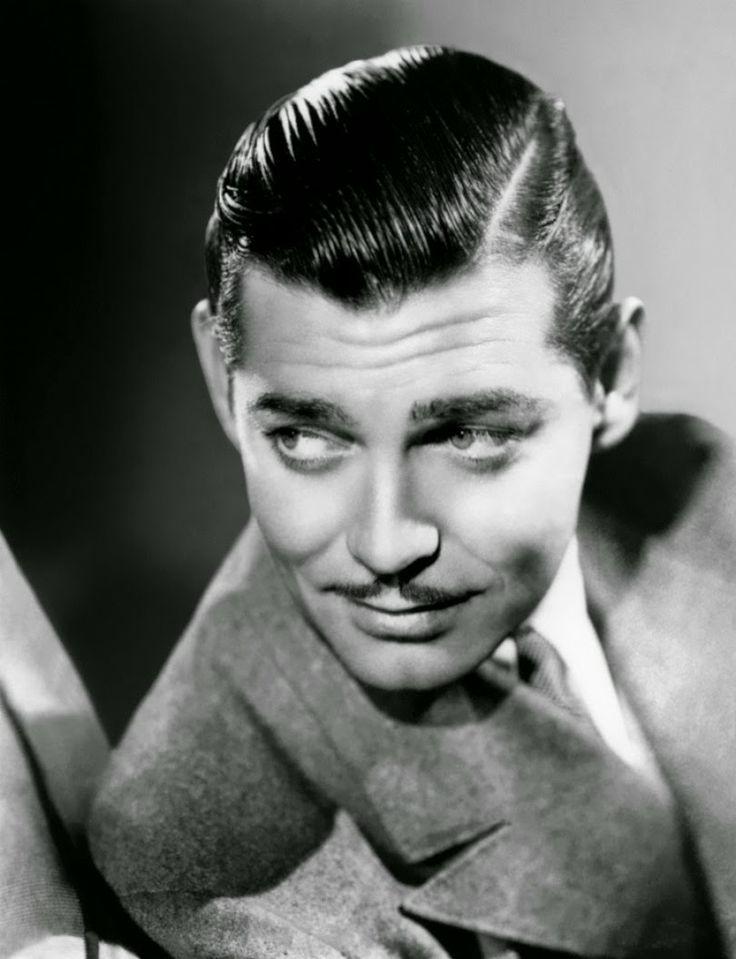 """Clark Gable. Corte de cabelo Razor Part, que vem a ser um corte feito na lateral do cabelo com uma navalha. tem influências militares, começou a ser adotado por volta da década de 1930. O cabelo bem """"lambido"""" é puxado para trás com auxílio de uma pomada capilar."""