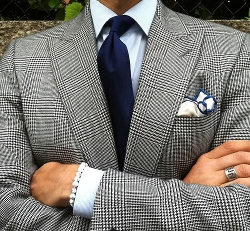 Light grey tweed jacket with peak lapels, white shirt with light blue hairline stripes, navy tie