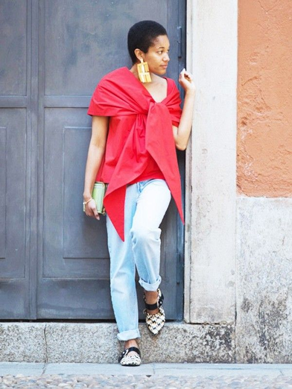Tamu McPherson in a striking red-top with jeans.