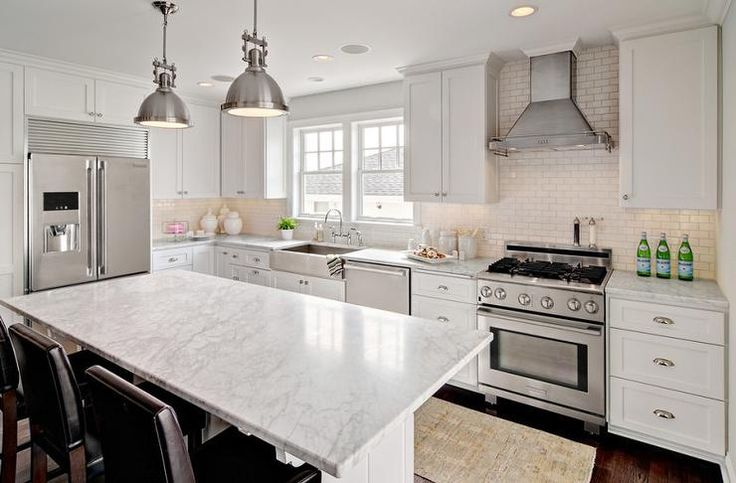 Amazing kitchen features white shaker cabinets paired with white marble countertops and a white mini brick tiled backsplash.