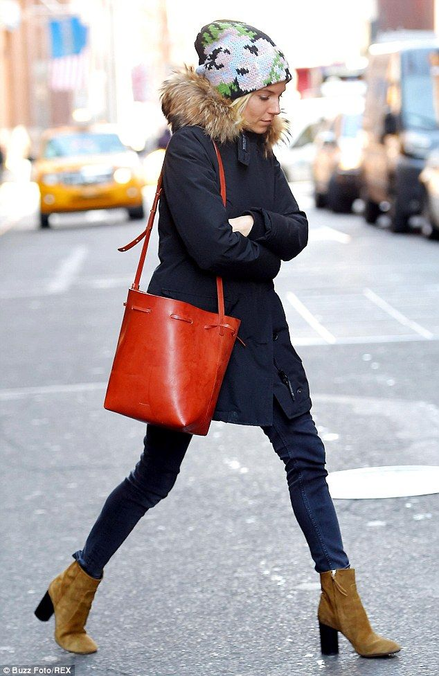 Red alert:Sienna covered up against the chill as she wore a colourful knitted hat and a fur collared black coat