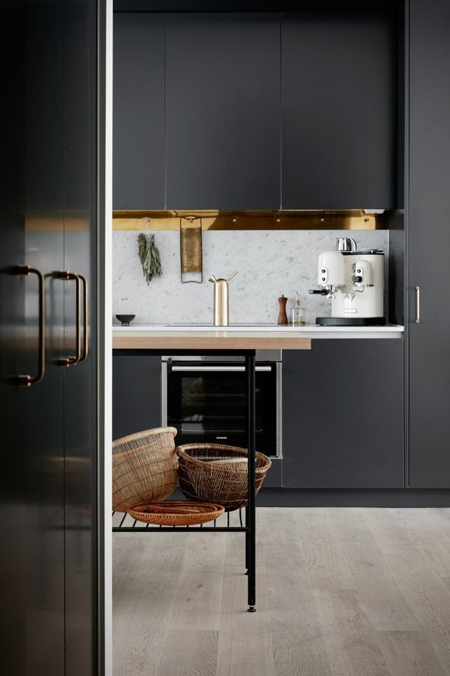 I've seen black kitchens with white marble worktops before and I think they are super nice, but this brass border on the top for hanging kitchen utensils really takes this one to another level. Such a