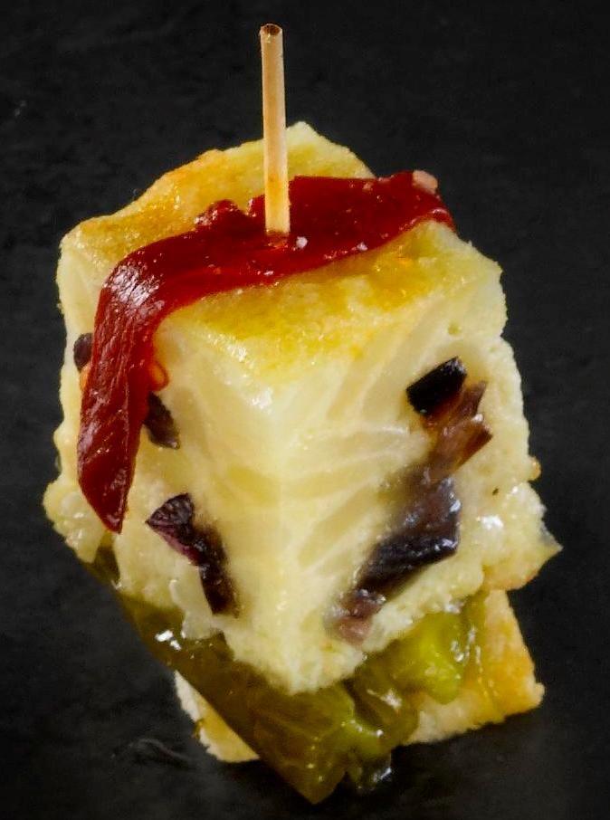 pinxo de tortilla  de patata y cebolla en lecho de pimientos