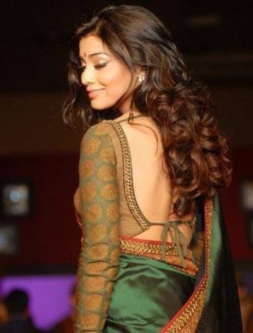 A saree that dips deep in the back with a long sleeve-contrast.