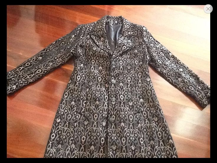 This exquisite black and gold design coat is so georgeous . Size 10, no label. Black background with a gold design throughout. Lined inside with four delicate buttons the length of the coat is 96cm there is also a band on the cuff area with the matching button.