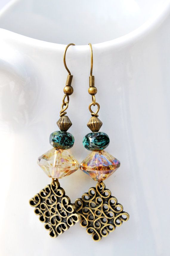The intricately carved brass diamonds are topped by beautiful amber and teal Czech glass beads. Both beads have a lovely Picasso finish which is a fun effect that sometimes resembles natural gemstones at first glance. The finish adds elements of brown or green to the surface of the bead in an irregular pattern. Brass ear wires Drop: approx. 3 7.62 cm Your earrings will be carefully placed in a box with cotton insert and mailed in a bubble mailer. To see more Beechtree earrings, please vie...