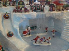 This is the center section of my friend Darcy's North Pole display. It features a waterfall with a frozen skating pond. There are 2 penguins swimming under the ice. There is a sledding hill that comes down from the upper level onto the skating pond and steps that can take the elves back up to the top.