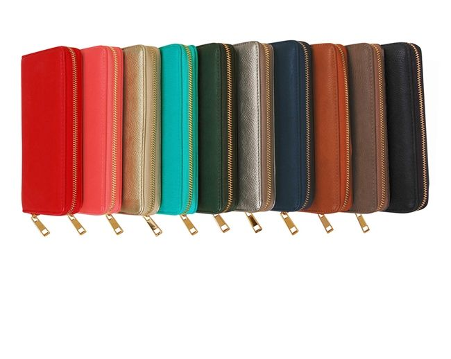 This chic vegan leather zip wallet features interior pockets, credit card slots, and gold hardware.