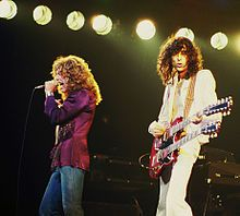 A colour photograph of Robert Plant with microphone and Jimmy Page with a double necked Gibson performing on stage.
