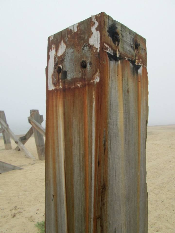 Rusty rainbow groyne post.